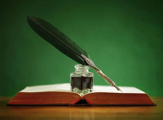 Quill pen and inkwell resting on book for content creation section