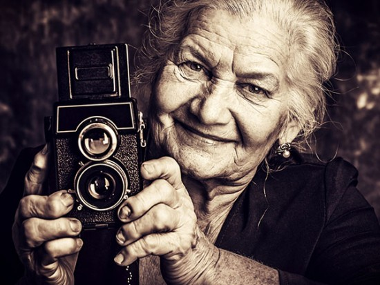 Image of adorable old woman with camera for photography services