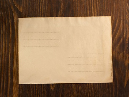 Antique envelope on wood background for mailing services section