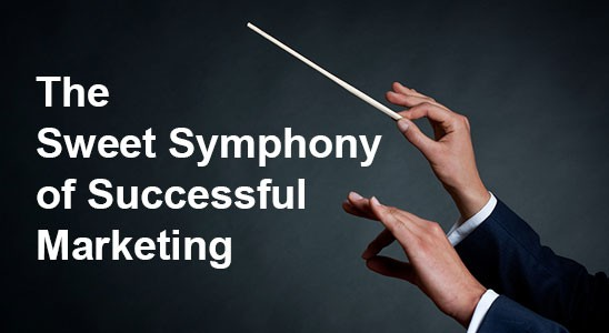 Pair of conductor's hands directing the words the sweet symphony of successful marketing