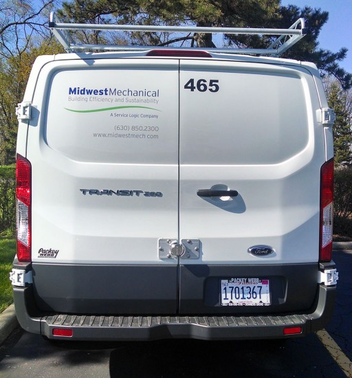 Rear view of vehicle graphics installation on white Transit van